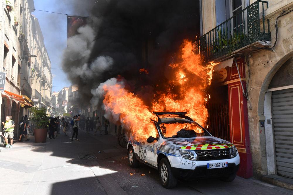 Carro da polícia incendiado por participantes do movimento rebelde coletes amarelos em Montpellier, na França