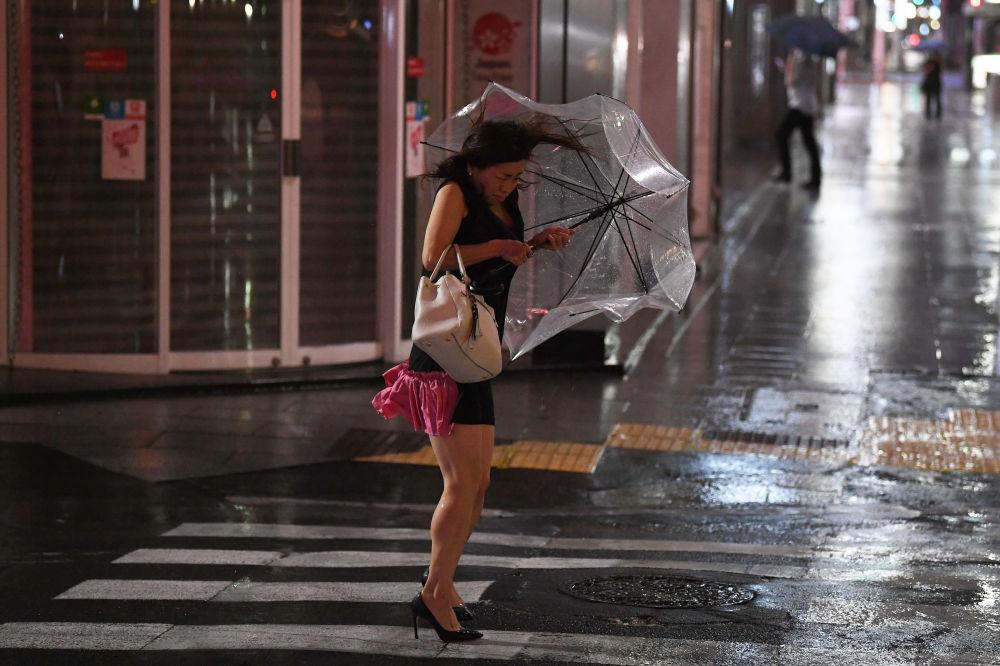 Mulher em Tóquio com guarda-chuva se tenta proteger da chuva e do vento forte