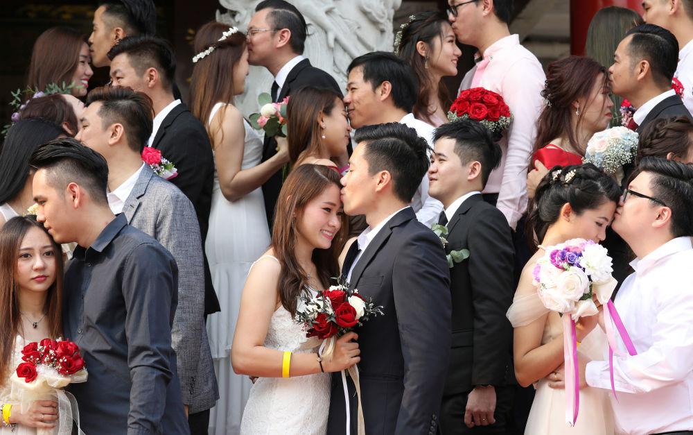 Recém-casados se beijam durante casamento em massa em Kuala Lumpur, Malásia