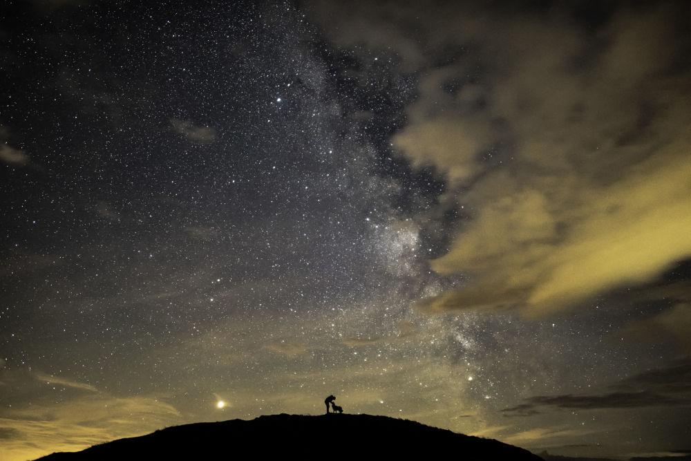 Imagem retrata o fotógrafo britânico Ben Bush, que ganhou o 1º lugar na categoria Pessoas e Espaço, na competição Insight Investment Astronomy Photographer of the Year 2019, cercado por Marte, Saturno e o núcleo galáctico da Via Láctea