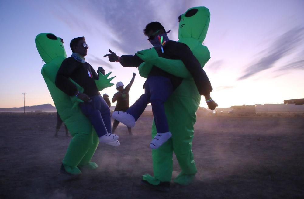 Participantes da invasão da Área 51 dançam vestidos como alienígenas, em Nevada