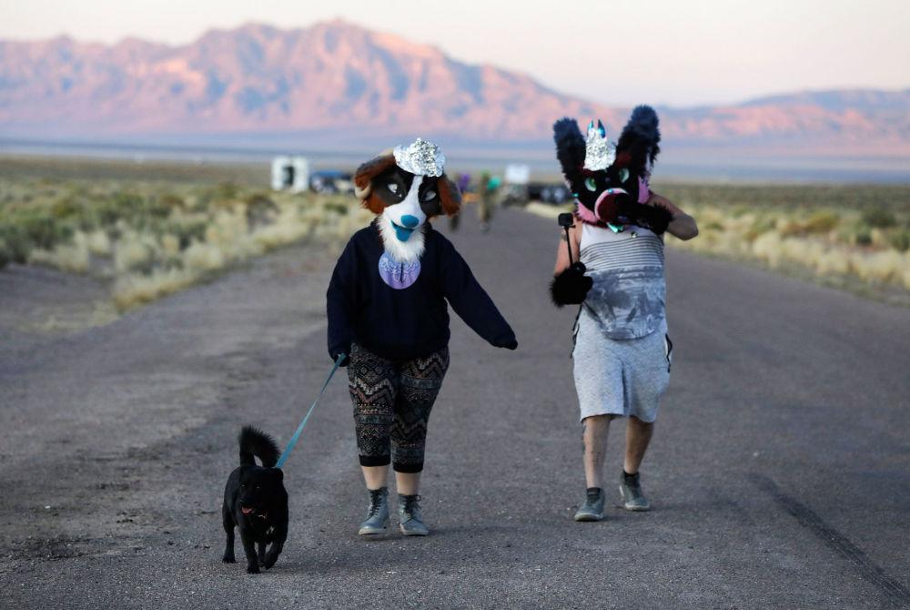 Participantes da invasão da Área 51 em Nevada caminham para uma entrada da Área
