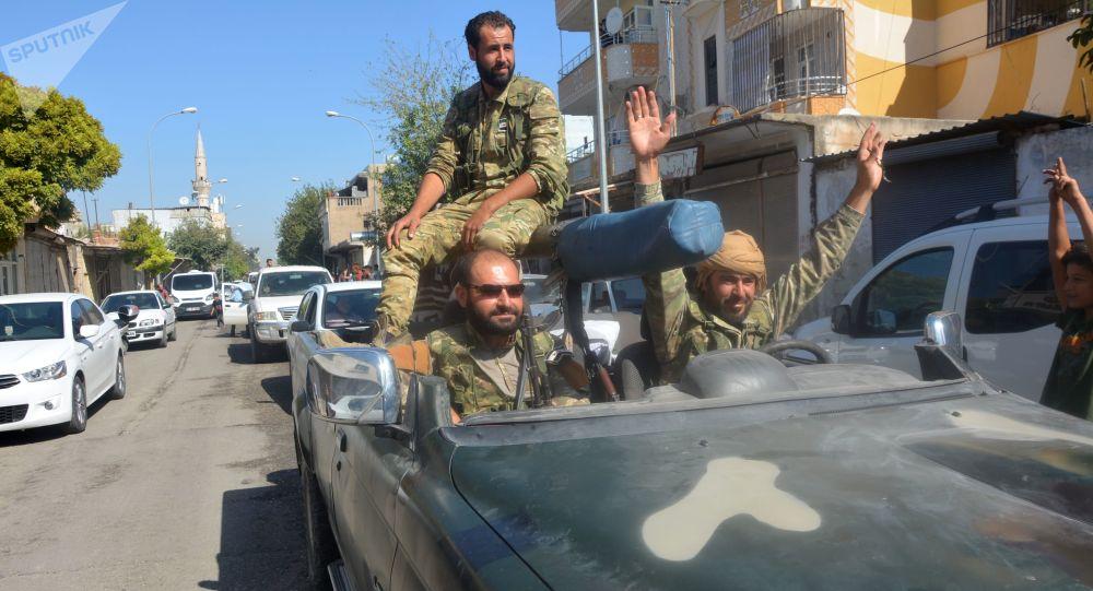 Militares do Exército Livre da Síria passando em veículos pela fronteira turco-síria após a Turquia ter lançado a operação militar Primavera da Paz no nordeste da Síria
