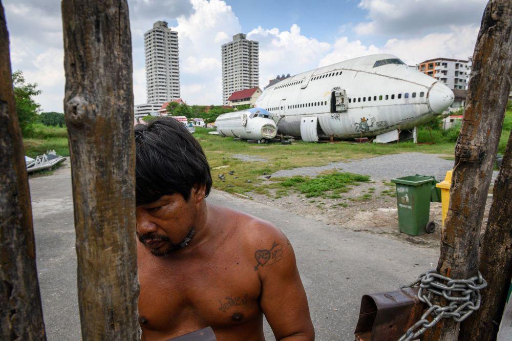 Homem cobrando entrada no portão em frente a aviões abandonados no local turístico chamado de cemitério dos aviões, nos subúrbios de Bankok