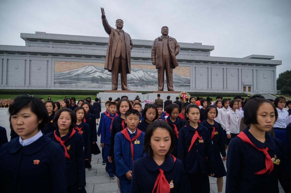 Estudantes em frente das estátuas dos líderes norte-coreanos Kim Il-sung e Kim Jong-il durante o 74º aniversário da fundação do Partido dos Trabalhadores da Coreia