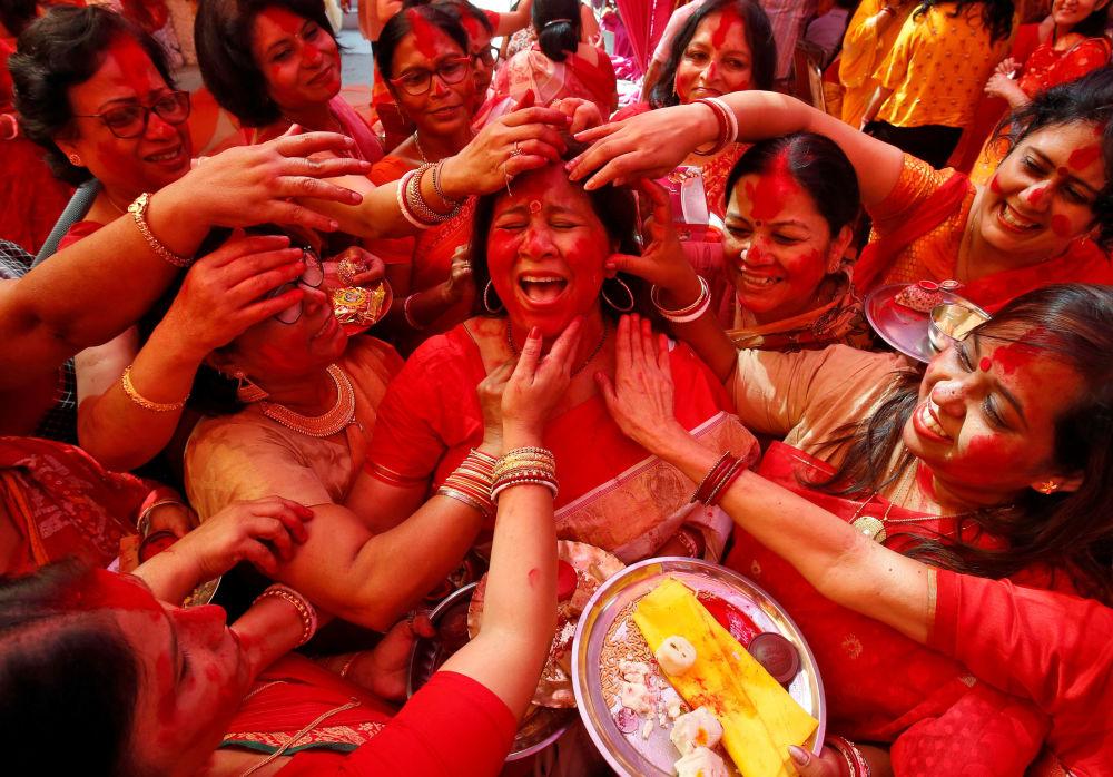 Mulheres indianas no festival da deusa Durga aplicando pó vermelho no rosto