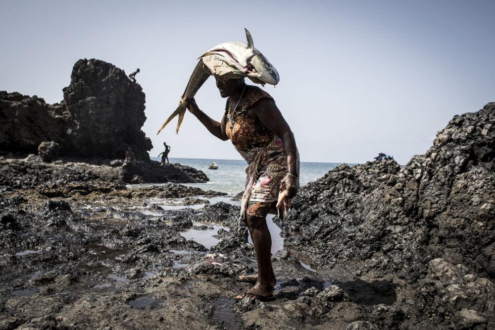 Mulher com peixe estripado na cabeça em pequeno vilarejo de Cabo Verde