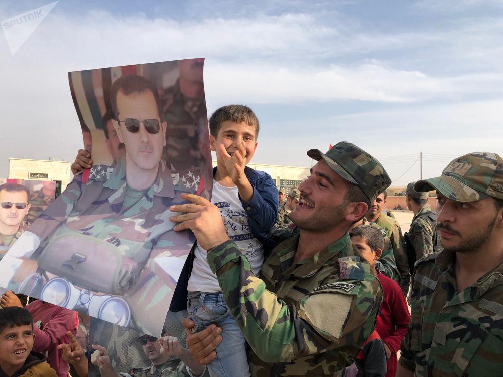 Crianças e militares seguram cartazes com a imagem do presidente da Síria, Bashar Assad, na cidade de Manbij, liberta pelo Exército sírio.