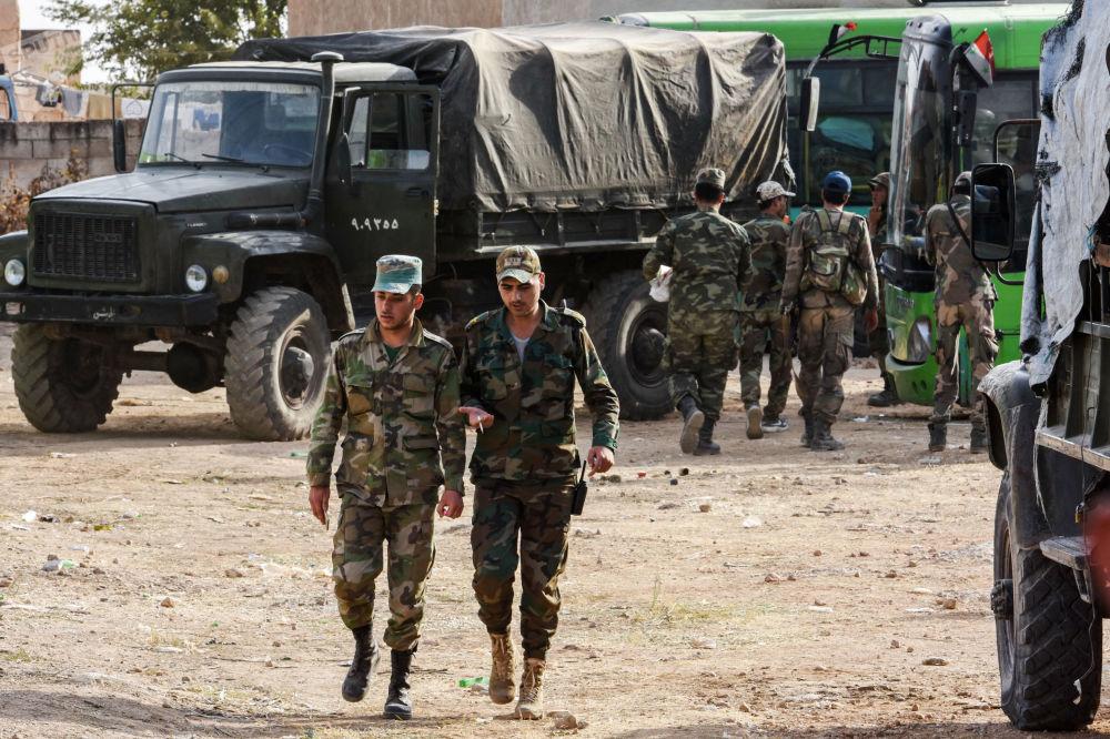Soldado caminha próximo a veículos militares do Exército sírio, na cidade de Manbij, no nordeste da Síria