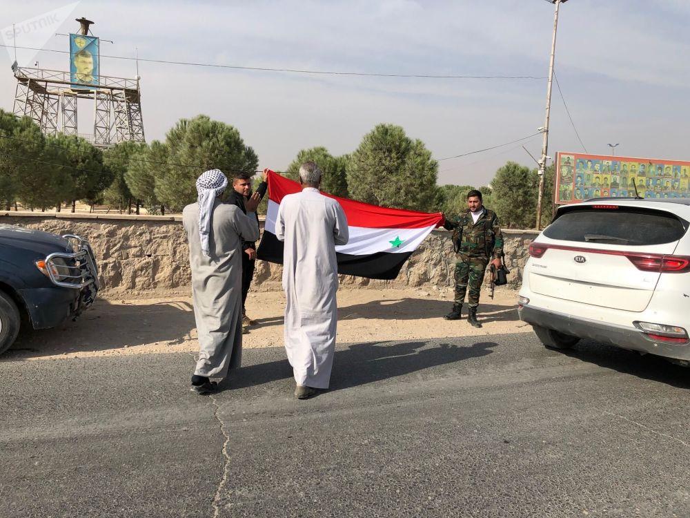 Moradores da cidade de Manbij se encontram com militares do Exército sírio.