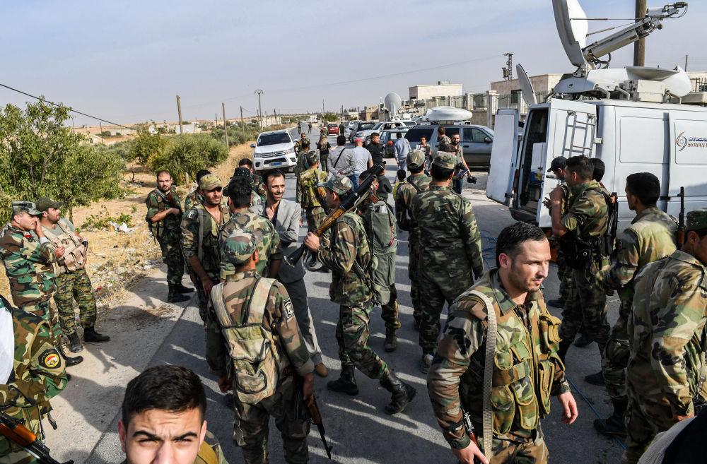 Forças sírias passam por jornalistas posicionados na cidade de Manbij, no nordeste da província de Aleppo