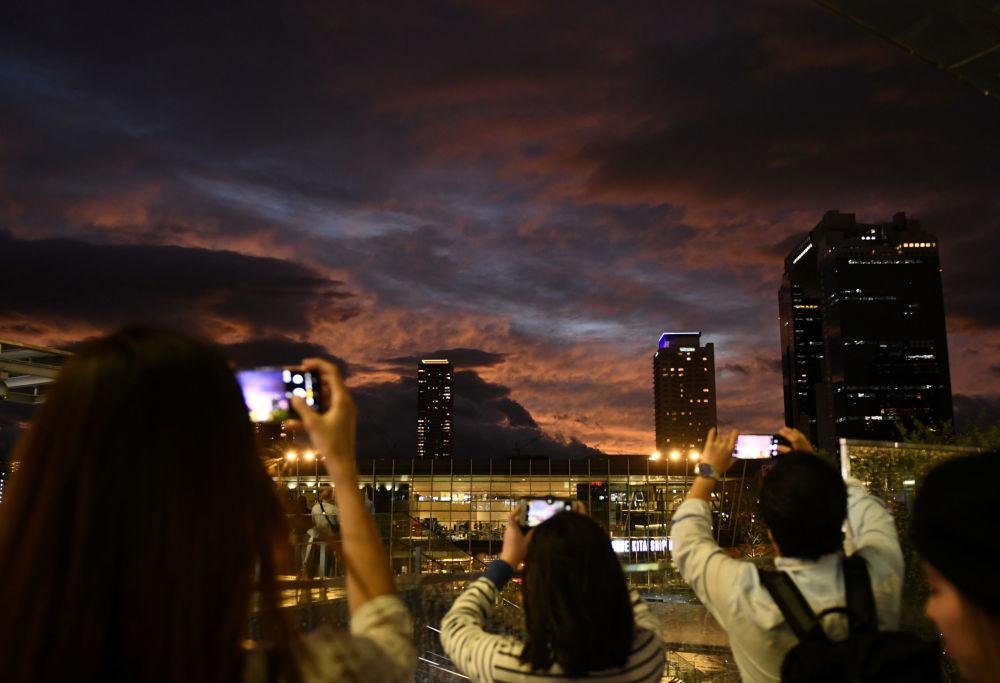 Pessoas tiram fotos do céu durante o pôr do sol durante a aproximação do tufão Hagibis da cidade de Osaka, Japão