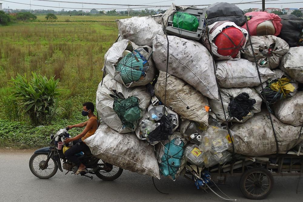 Lixeiro transporta resíduos plásticos para reciclagem em Hanói, no Vietnã