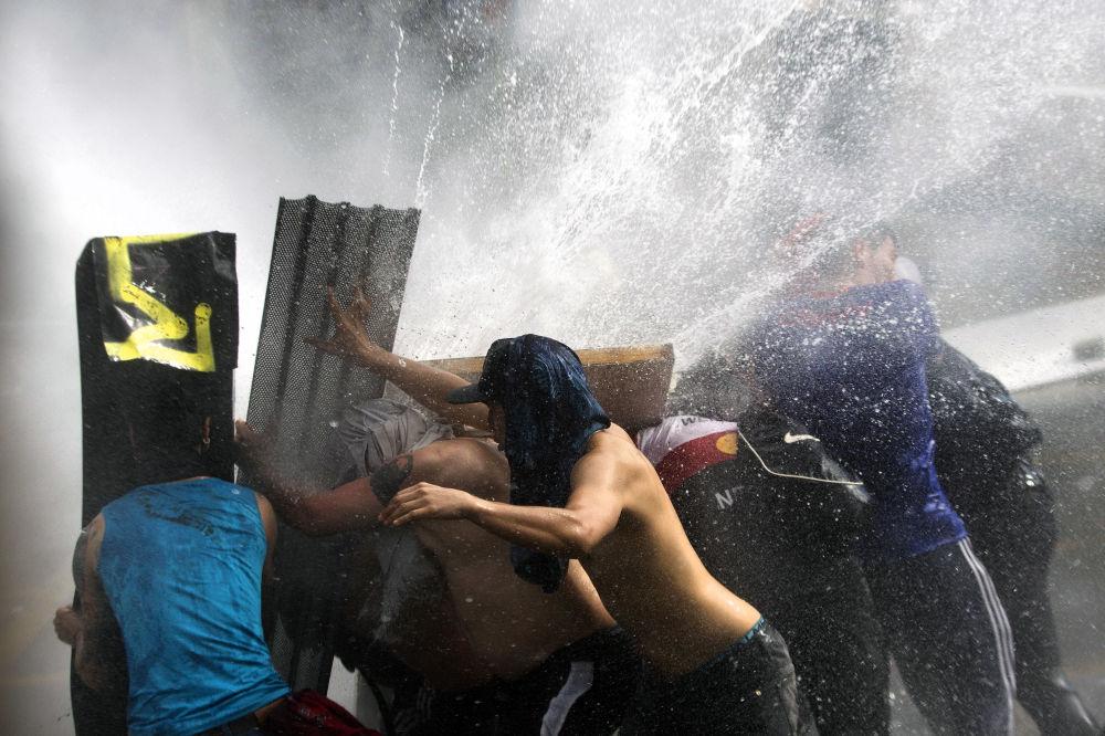 Manifestantes tentam se proteger de jatos de água jogados pela tropa de choque para dispersar manifestantes