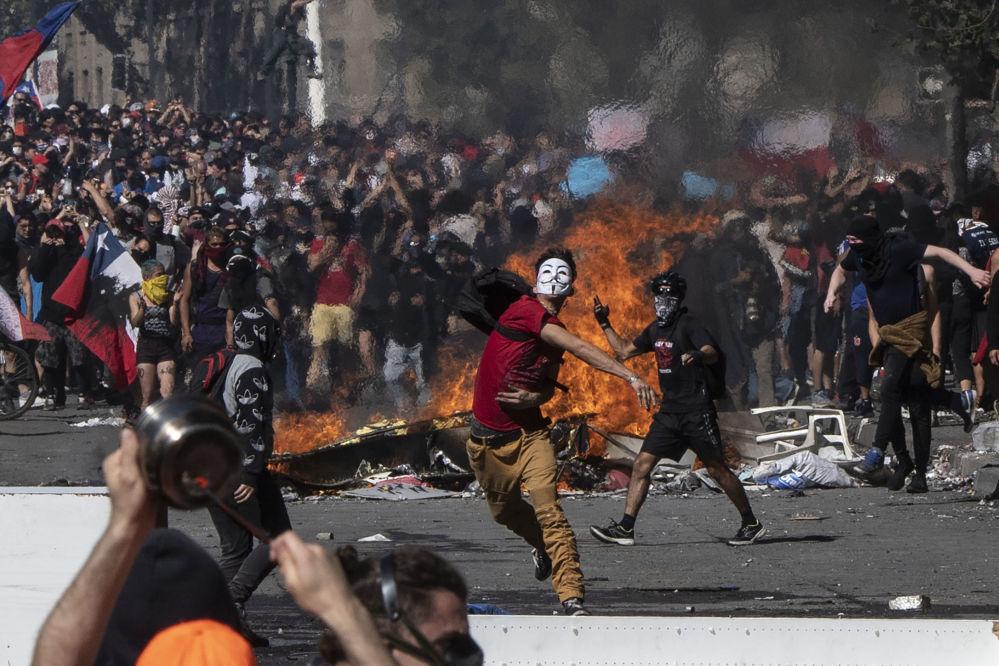Manifestantes montam barricadas e cobrem o rosto durante protestos no Chile
