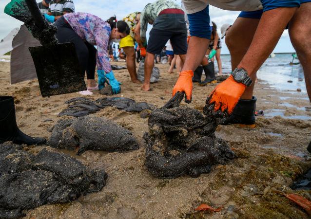 Voluntários trabalham para remover óleo na praia de Suape, em Cabo de Santo Agostinho, no estado de Pernambuco, Brasil. Foto de 20 de outubro de 2019.