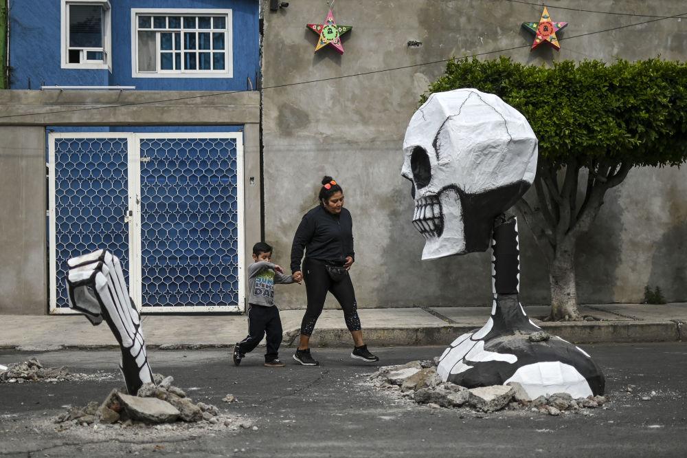 Mulher com uma criança caminhando diante de uma escultura na véspera do Dia dos Mortos no México. Foto tirada em 28 de outubro