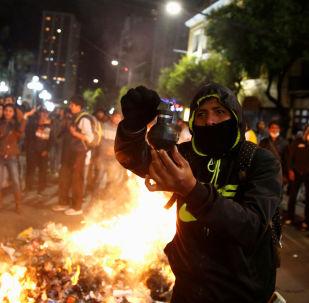 Manifestante segura uma bomba de gás lacrimogênio nas mãos, em meio à conflitos entre manifestantes na Bolívia, no dia 5 de novembro