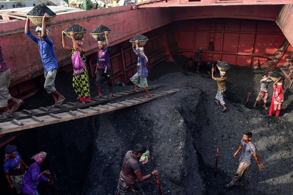 Trabalhadores descarregam navio com carvão em Gabtoli, Bangladesh