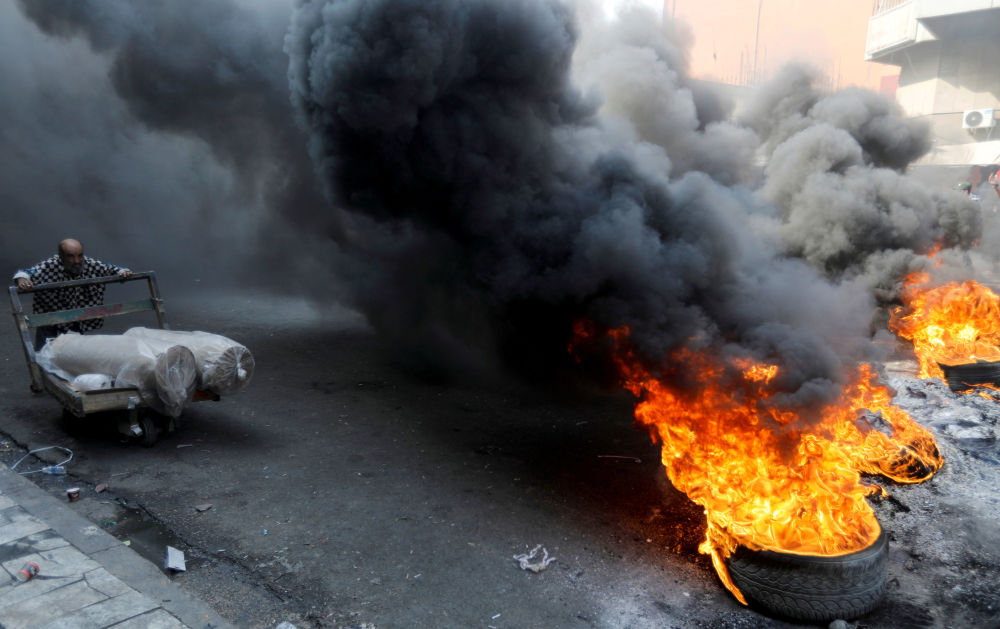 Pneus em chamas durante protestos contra o governo iraquiano na capital Bagdá