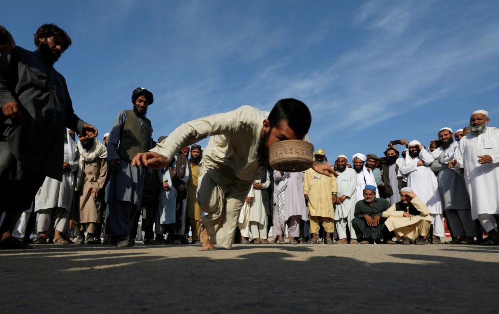 Simpatizante do partido político e religioso JUI-F jogando o jogo tradicional do Chapéu em Islamabad, Paquistão