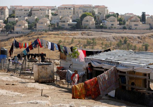 Crianças palestinas brincam próximas ao assentamento israelense de Maale Adumim, na Cisjordânia ocupada, em julho de 2019