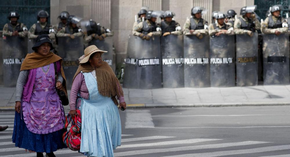 Mulheres passam na frente do palácio presidencial da Bolívia, que está sob forte proteção militar e policial, em 19 de novembro de 2019