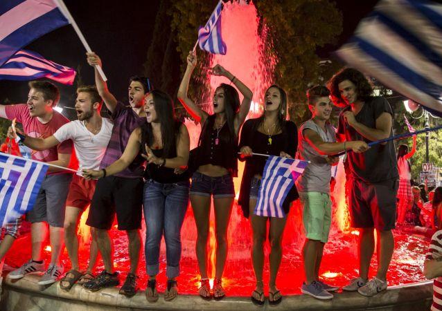 Apoiantes de Não voto celebram resultados do referendo em uma rua no centro de Atenas no 5 de julho 2015.