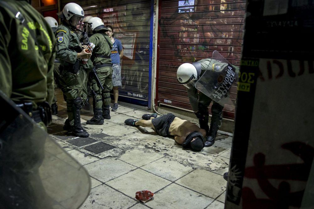Polícia e um manifestante ferido na luta depois do anúncio dos resultados do referendo em Atenas, Grécia.