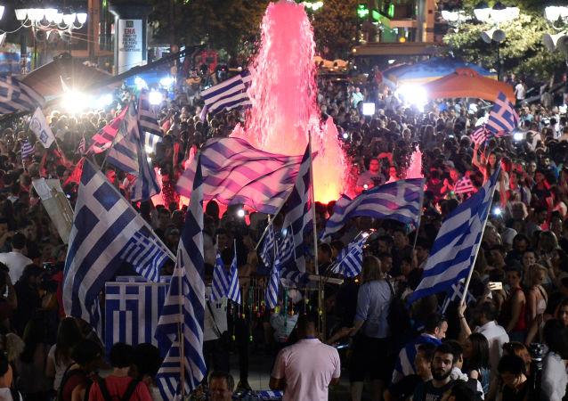 As pessoas celebram os resultados do referendo em Atenas.