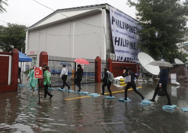 Pessoas caminham em ruas alagadas após tufão Kammuri