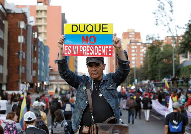 Manifestante exibe cartaz contra o presidente da Colômbia, Iván Duque, durante protesto em Bogotá, capital do país, em 25 de novembro de 2019