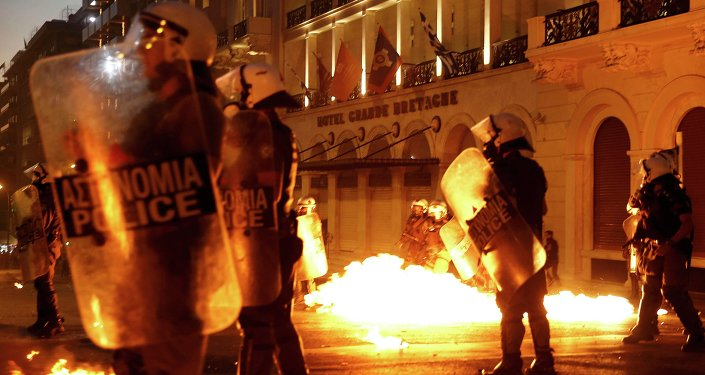 Riot police stand amongst the flames from exploded petrol bombs thrown by a small group of anti-austerity demonstrators in front of parliament in Athens, Greece July 15, 2015