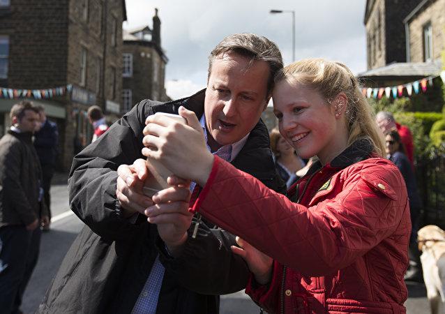 Premiê britânico David Cameron tira selfie com uma menina durante a campanha das eleições em 3 de maio de 2015