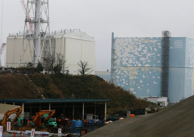 A part of the roof of a building covering the Unit 1 reactor, left, is seen removed at the Fukushima Dai-ichi nuclear power plant in Okuma, Fukushima prefecture, northeastern Japan, Wednesday, Nov. 12, 2014