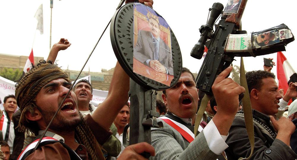 Manifestantes iemenitas seguram rifles com fotos do ex-presidente do país Ali Abdullah Saleh durante um ato contra os ataques aéreos realizados pela coalizão liderada pela Arábia Saudita contra os houthis na capital Sanaa em 3 de abril de 2015