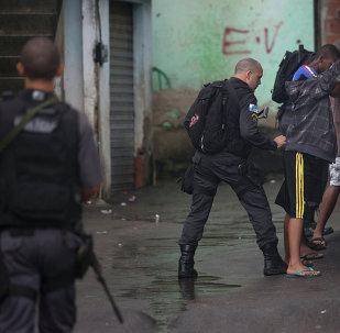 Policiais da Unidade de Polícia Pacificadora (UPP) revistam moradores do complexo de favelas do Alemão no Rio de Janeiro