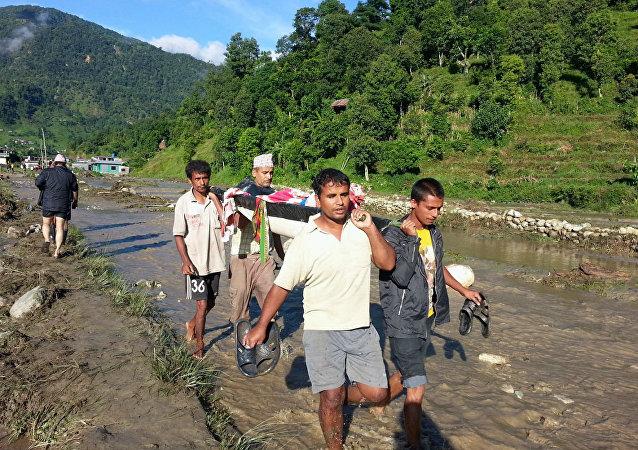 Moradores de um dos vilarejos atingidos por delizamentos no Nepal socorrem uma vítima.