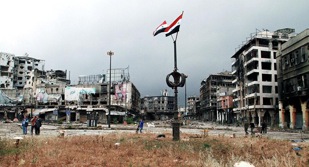 Duas bandeiras nacionais da Síria e os funcionários do governo incepcionando os danos na cidade de Homs, Síria