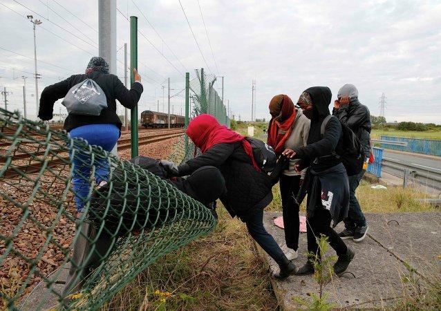Imigrantes tentando abrir caminho através de cerca na Europa