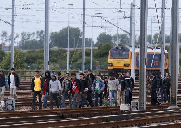 Imigrantes seguem ao longo de linha férrea em sua tentativa de atravessar o túnel do Canal da Mancha próximo a Calais, França, 29 de julho de 2015