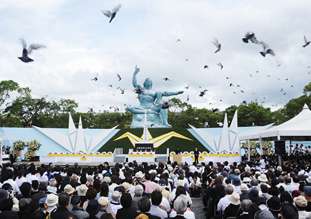 Pombos voam em torno da estátua de paz durante um serviço memorial para as vítimas do bombardeio atômico 1945, no Parque da Paz de Nagasaki em 9 de agosto de 2014.