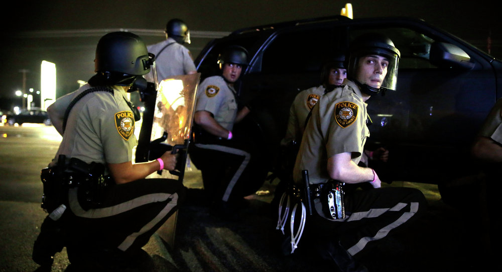 Policiais de Ferguson se escondem atrás de veículo durante manifestações um ano após a execução do jovem negro Michael Brown
