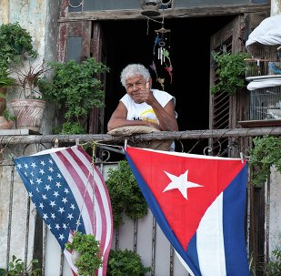 Cubano acena positivamente de sua varanda decorada com as bandeiras dos EUA e de Cuba