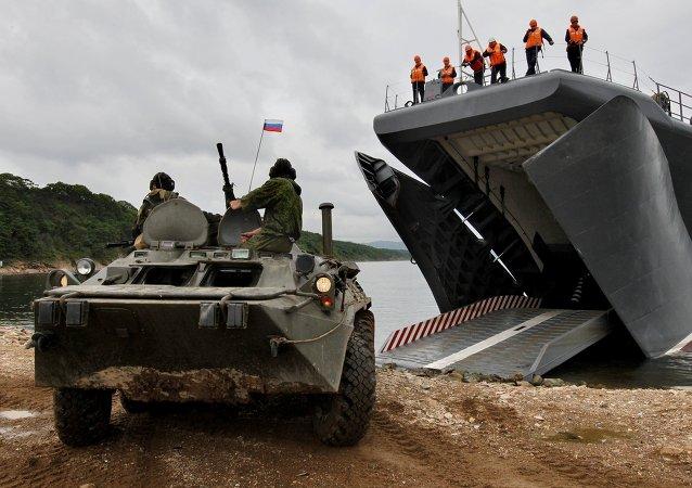 O navio russo desembarca os veículos blindados (BTR) durante os exercícios navais sino-russos Cooperação Naval 2015.