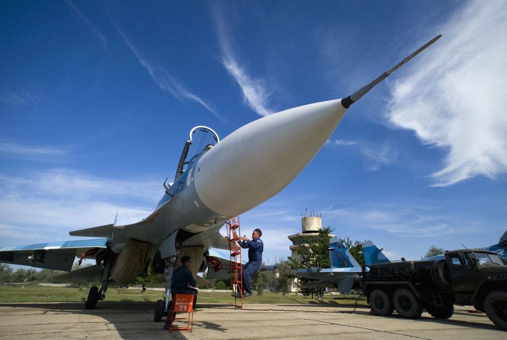 Militares russos preparam o avião Su-33 para o voo de treinamento no polígono dos sistemas de decolagem e aterrissagem para forças da aviação naval Nitka na Crimeia (Rússia).