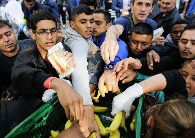 Imigrantes recebem alimentos de voluntários enquanto esperam pelo registro no centro de recepção para refugiados e asilados em Berlim nesta sexta-feira, 5 de setembro.