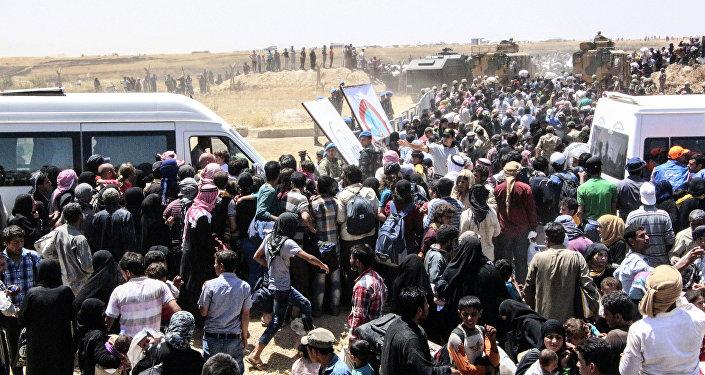 Refugiados síriosà espera de transporte após atravessar a fronteira com a Turquia da cidade síria Tal Abyad