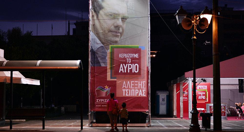 Mulher e criança olham cartaz eleitoral do partido Syryza e seu líder, Alexis Tsipras, em Atenas, na Grécia