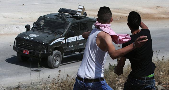 Jovens palestinos lançam pedras contra veículo policial israelense